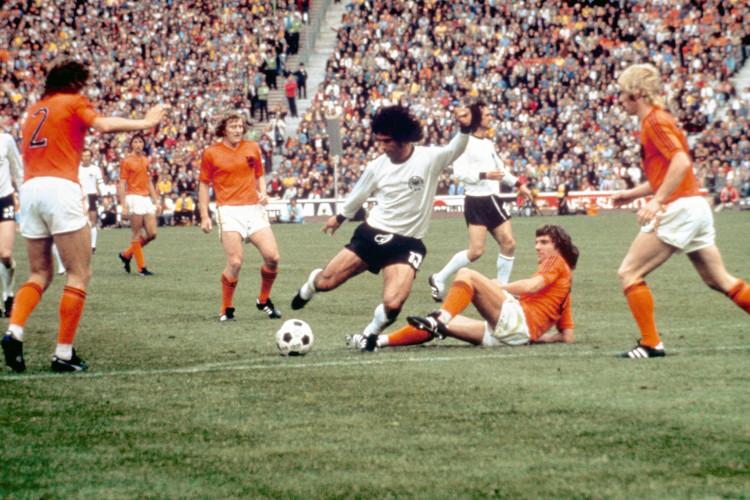 Der deutsche Stürmer Gerd Müller (M) läßt sich von den ihn umzingelnden Niederländern scheinbar nicht beeindrucken und bereitet jenes Tor vor, das Deutschland zum Weltmeister machen wird, er schießt das 2:1-Siegtor:  Am 07.07.1974 gewinnt die deutsche Nationalmannschaft in München das Finale der 10. Fußball-Weltmeisterschaft gegen das Team der Niederlande. Deutschland ist Weltmeister. Müllers vier Tore in diesem Turnier und seine zehn Tore bei der WM 1970 machen ihn zum erfolgreichsten WM-Torschützen der Geschichte.